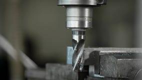 Mordido da máquina de perfuração industrial está girando em uma fábrica, close-up dela, trabalhador está limpando a coroa pela es vídeos de arquivo