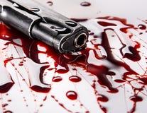 Mordkonzept - schießen Sie mit Blut auf weißem Hintergrund Stockbild