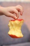 Mordu d'une pomme dans une main de t Image libre de droits