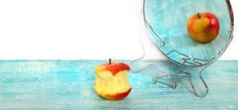 Mordu de la pomme et de la réflexion dans un miroir de la pomme entière Photographie stock libre de droits