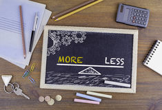 More and Less Balance. Chalkboard on wooden office desk stock photography