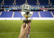 More dollars more titles with the background of a stadium Royalty Free Stock Photography
