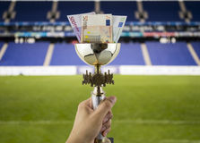 More euros more titles with the background of a stadium. Hand lifting a trophy with euros in more money concept with more titles fund a stadium Royalty Free Stock Photography