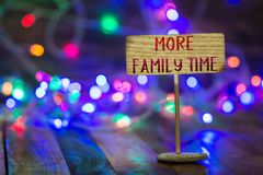 More family time on small sign board. More family time written on small wooden sign board on wooden table with Christmas light and bokeh background royalty free stock images