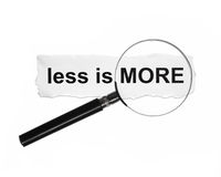 Less is more. Magnifying glass and word less is more on paper royalty free stock images