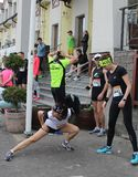 Runners doing stretching before a start of a running competition royalty free stock images