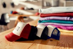 More than you expect. Custom apparel, clothes neatly folded on shelves. Stack of colorful clothing and baseball cap in