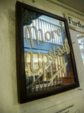 More Upstairs Sign. Brown wooden framed mirror with painted on cursive letters saying More Upstairs with arrow at an antique thrift store in Hay-on-Wye, Wales Stock Photography
