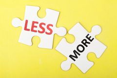 Less and more words. Printed on two pieces of puzzle Royalty Free Stock Photos