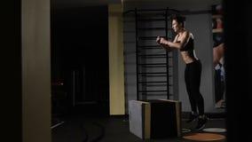 A morena atlética bonito que faz algum salto exercita em um gym do cruz-treinamento filme
