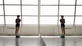 A morena atlética caucasiano endireita seu sportswear, olhando em um espelho vídeos de arquivo