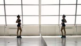 A morena atlética caucasiano endireita seu sportswear, olhando em um espelho filme