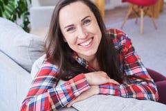 Morena atractiva que sonríe y que tiene resto que se sienta en el sof elegante Imágenes de archivo libres de regalías