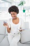 Morena atrativa alegre usando seu PC da tabuleta para comprar em linha Imagens de Stock Royalty Free