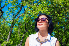 Morena atrativa nos óculos de sol que descansam no parque Imagem de Stock
