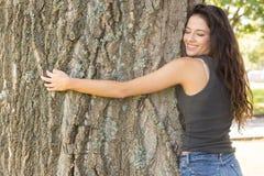 Morena atrativa ocasional que abraça uma árvore com olhos fechados imagem de stock