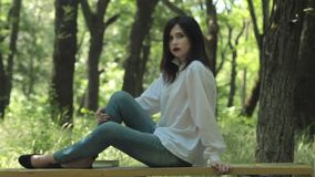 Morena atrativa que senta-se no banco no parque filme