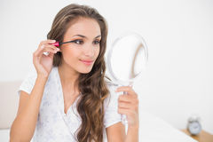 Morena atrativa satisfeita que aplica o rímel e que guarda o espelho Fotografia de Stock Royalty Free
