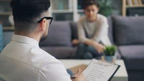 Morena barbuda del psic?logo que habla con el paciente femenino en la oficina que sostiene el papel almacen de metraje de vídeo