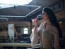 A morena bonita com cabelo longo está bebendo a posição de um vidro do vinho tinto dentro foto de stock