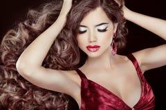 Morena bonita com cabelo ondulado longo e levantamento vermelho 'sexy' dos bordos Imagem de Stock