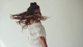 Morena bonita da mulher que levanta no estúdio no fundo branco e que anda à câmera video estoque