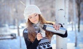 A morena bonita derrama o café de uma garrafa térmica para uma caminhada no inverno fotografia de stock royalty free