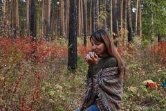 Morena bonita em um parque do outono com um copo do café quente foto de stock royalty free