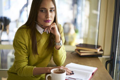 Morena bonita em uma blusa amarela no diário para criar caráteres dos desconhecido fora da janela Fotos de Stock Royalty Free