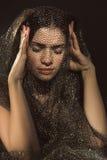 A morena bonita guarda suas mãos atrás de sua cabeça Fotografia de Stock Royalty Free