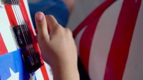 A morena bonita joga a guitarra na sala clara do estúdio Em uma guitarra o desenho da bandeira americana A menina filme