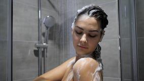 Morena bonita na espuma que toma o chuveiro na água quente, close-up video estoque