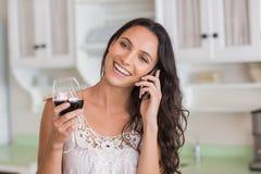 Morena bonita no telefone que come o vidro do vinho Imagens de Stock Royalty Free