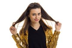 A morena bonita nova em um revestimento do ouro mantém o cabelo e o sorriso das mãos Foto de Stock Royalty Free