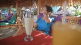 A morena bonita nova está apreciando suas férias na barra da ilha tropical que senta-se na tabela Viajante fêmea video estoque