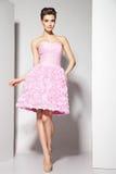 Morena bonita nova no vestido cor-de-rosa no branco Imagem de Stock Royalty Free