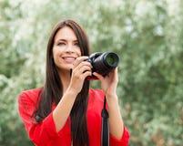Morena bonita nova que está feliz com a câmera nova da foto do slr imagens de stock royalty free