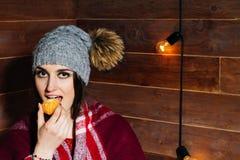 Morena bonita nova que sorri na roupa e no tampão do inverno com as tangerinas no fundo de madeira Foto de Stock Royalty Free