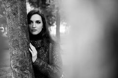 Morena bonita que está a árvore próxima no parque Retrato preto e branco da mulher bonita com bordos sensuais e Fotografia de Stock Royalty Free
