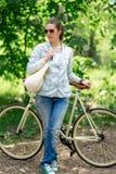 Morena bonita que está perto de sua bicicleta amarela Imagens de Stock Royalty Free