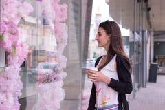Morena bonita que guarda uma xícara de café e que olha a loja Foto de Stock Royalty Free