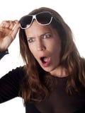 Morena bonita que mantém seus óculos de sol chocados acima Fotografia de Stock Royalty Free