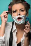 Morena bonito em encrespadores de cabelo e espuma que levanta com imagens de stock royalty free