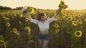 Morena bonito em um campo de florescência do girassol filme