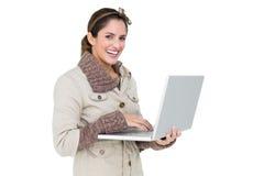 Morena bonito feliz na forma do inverno que guarda o portátil Imagens de Stock
