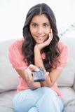 Morena bonito surpreendida que senta-se no sofá que guarda o telecontrole Fotos de Stock Royalty Free