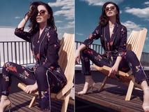 Morena brilhante lindo no vestido vívido que senta-se em uma cadeira de madeira foto de stock royalty free