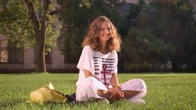 Morena caucasiano de sorriso dos jovens que senta-se no parque na grama, olhando in camera, rindo, universidade no fundo vídeos de arquivo