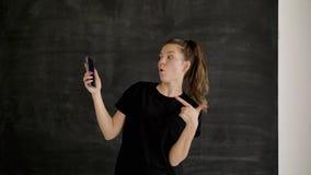 A morena caucasiano no sportswear guarda um smartphone em sua mão e mostra a classe vídeos de arquivo