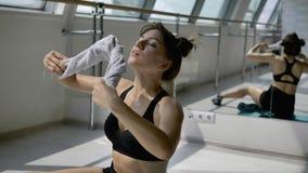A morena caucasiano no sportswear preto está esfriando fora com a toalha branca no assoalho vídeos de arquivo